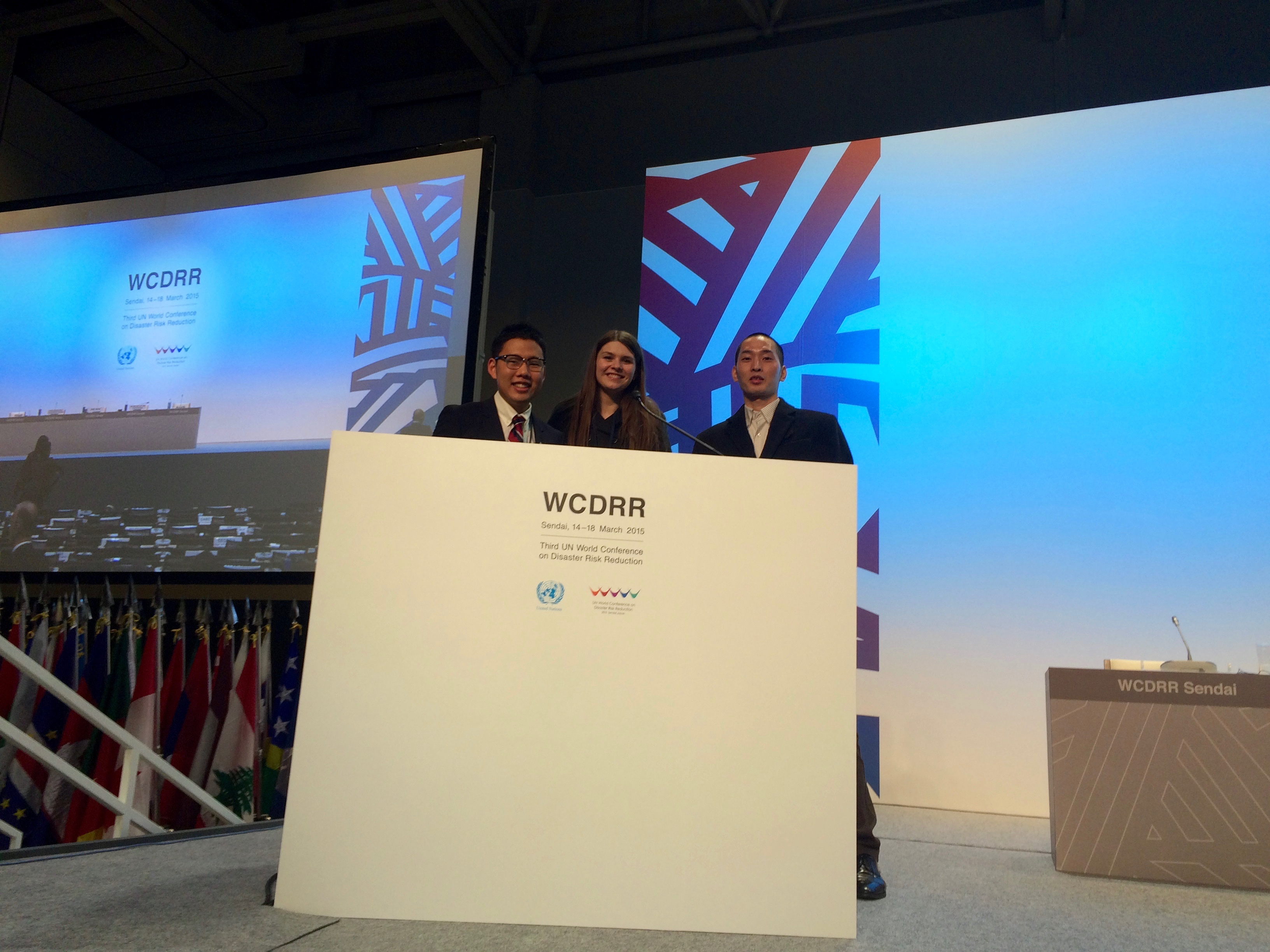 第三回国連世界防災会議の国際会議場の壇上で撮ったインターンの仲間との写真。一番左が高坂さん